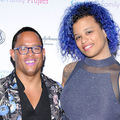 Black transgender person in multicolored blazer and black dress shirt and dark grey jeans stands next to Black transgender woman in blue dress in front of light grey background with blue and pink text and black insignia