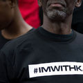 Black man in black tshirt with black text in white box in front of Black boy in black t-shirt and crowd in multicolored clothing
