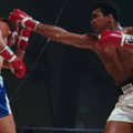 Black man in black and white shorts and red and white boxing gloves punches White man in blue and white shorts and red and white boxing gloves in front of black background
