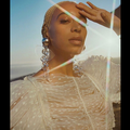 Black woman with blonde hair and beige dress in front of yellow sunlight and blue sky