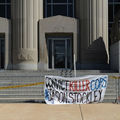 White sign with red and blue and black text hangs on grey barrier with yellow and black police tape in front of brown and grey courthouse