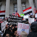 Brown men and women in multicolored clothing wave multicolored signs and red and black and white flags and red and white and blue flags in front of grey building