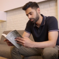 Brown man in navy collared shirt and brown pants holding grey book while sitting on brown couch in front of white wall