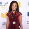 Black woman in red dress with bronze medal on black lanyard in front of light grey wall with purple and yellow text and insignia