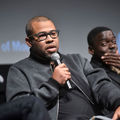 Black man in black shirt and grey jacket holds black and grey microphone next to Black man in brown shirt and black jacket in front of black wall and dark screen with white text