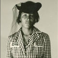 Sepia image of Black woman in black-and-white patterned dress and hat in front of brown background