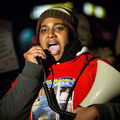 Black woman in red t-shirt and brown striped hat and black scarf speaks into black receiver attached to brown megaphone in front of black sky