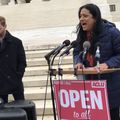 "Latina woman speaks at a rally in front of the Supreme Court with a sign that says ""Open to All"""