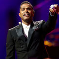 Black man in black tuxedo with white shirt holds black microphone in front of purple screen