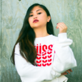 Asian woman in white sweatshirt with pink text in front of light blue wall