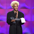 Black woman with blonde hair in black suit holds grey awards statue and white paper behind black microphone and stand in front of purple screen