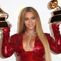 Black woman wears red dress and holds two gold award statues with brown bases in front of light grey wall with yellow insignia
