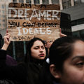 "A young Brown woman holds up a sign that says ""I am a Dreamer. You can't deport ideals"" at a New York City protest"