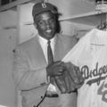 Black-and-white photo of Black man in baseball cap and suit holding baseball jersey and glove in front of lockers