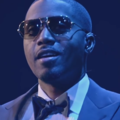 Black man in navy suit and bowtie and white shirt and brown sunglasses in front of black background