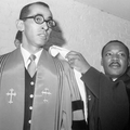 Black-and-white image of Black man in grey suit and pastor robes next to Black man in black pastor robes in front of grey wall