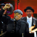 An elderly Black man in a suit holds up a fist during a jazz performance