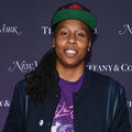 Black woman with black dreadlocks in black baseball cap with red insignia and navy jacket over purple shirt with pink text and greyscale image in front of purple-navy wall with white text