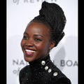 Black woman in black dress with grey buttons smiles in front of white wall with black text