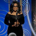 Black woman in black glasses and dress smiles and holds gold award statue behind black microphone and stand and in front of blue screen with gold circles