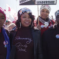 Three Black women wearing hats and pins at a political rally in Las Vegas.