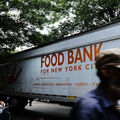 """White semi truck with orange lettering that reads, """"New York Food Bank"""" on city street"""
