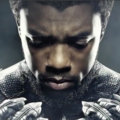 A closeup of a muscular Black man in a gray costume with sharp metal nails