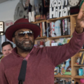 Black man in maroon sweater and hat and brown sunglasses hold up one finger while standing behind black microphone and in front of brown and grey wall and cabinets