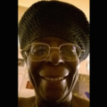 Smiling Black woman wearing glasses and knit cap