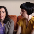 Two women sit next to each other on a couch