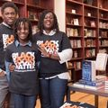 A Black man and a Black woman pose with a pre-teen Black child in a bookstore