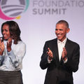 Michelle and Barack Obama smiling on stage
