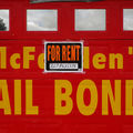 "Red garage door with ""McFadden's Bail Bonds"" painted on it in yellow, ""For Rent"" sign posted over the lettering"