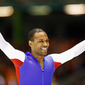 Black man in red and white and blue skating uniform smiles in front of blurry brown and red and green background