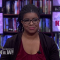 April Reign. Black woman with twists in her hair, large hoop earrings, maroon shirt and black jacket sits on television news set