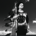 Black-and-white photo of Indigenous woman in traditional dress holding traditional Native American tool with multiple feathers in front of sky with clouds