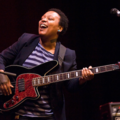 Black woman in navy blazer and dark and light blue striped shirt holds black bass with brown pick guard in front of black background and behind black microphone stands