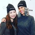"""An Afro-Latina and Asian wearing beanies that say """"roxanne roxanne"""" standing close to each other smiling"""