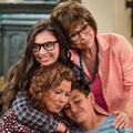 Two Brown women and one Brown girl and one Brown boy in multicolored clothing hug in front of blue dresser and brown walls