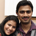 Brown woman in red sari next to Brown man in purple shirt and grey suit jacket in front of beige wall