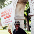 "Willie Hudspeth. Black man holds white sign with red lettering that reads, ""Please move statue to Confederate museum. God said, 'Love everybody.'"""