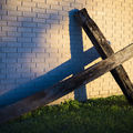 A wooden cross resting on its side, leaning against a building