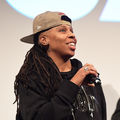 Black woman with black and brown dreadlocks in brown baseball cap and black hooded sweatshirt and t-shirt with gold letters hold black microphone in front of brown wall with white light