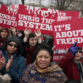 """Crowd of protesters hold red and white signs that read, """"It's about freedom"""" and """"Unrig the system."""""""
