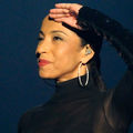 Black woman with black hair holds hand to forehead in black blouse in front of dark blue background