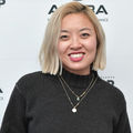Asian woman with blonde hair in black sweater in front of white wall with black logos and text
