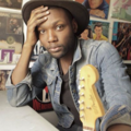 Black man in brown hat and blue denim shirt and grey t-shirt sits next to brown guitar head in front of multicolored posters on white wall