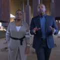 Black woman in brown dress with white stripes and black belt walks next to Black man in navy suit and blue shirt in front of suspended brown blacks and brown floor and ceiling