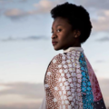 Black woman with black hair in blue and pink and brown and white cloak and pink and blue sky