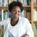 Black woman with black hair in white sweater and shirt smiles while sitting on green chair in front of brown bookshelf with multicolored books